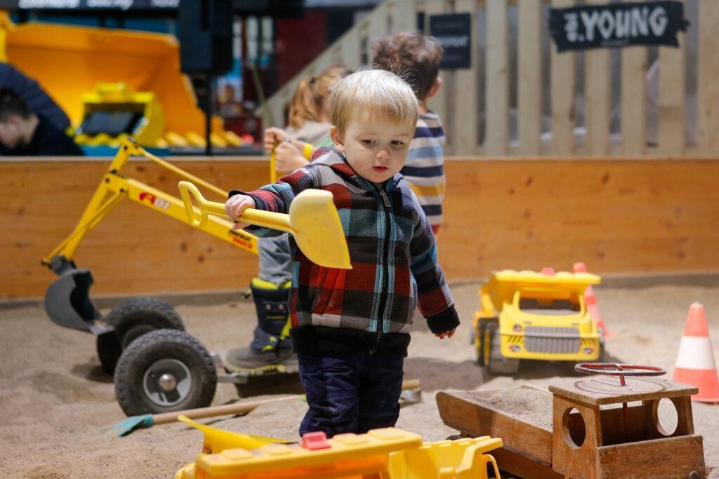 Schaufeln im grossen Sandkasten beim Kinderspielplatz